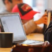 Mann sitzt vor einem Laptop in einem Cafe und arbeitet.